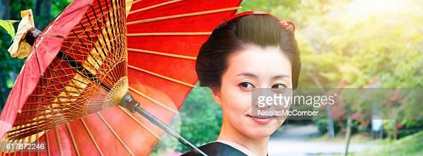 Japanese woman smiles back under red parasol panorama