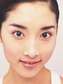 Japanese woman smiling and looking at camera, close up