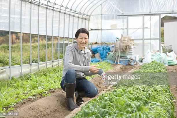 Japanese woman smiling in a plastic greenhouse