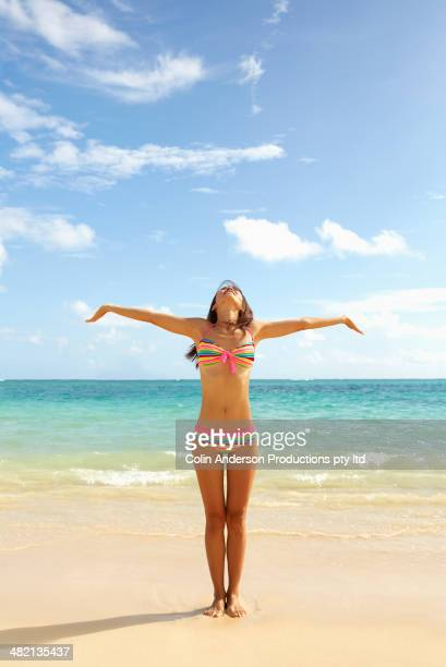 Japanese woman standing on beach with arms outstretched