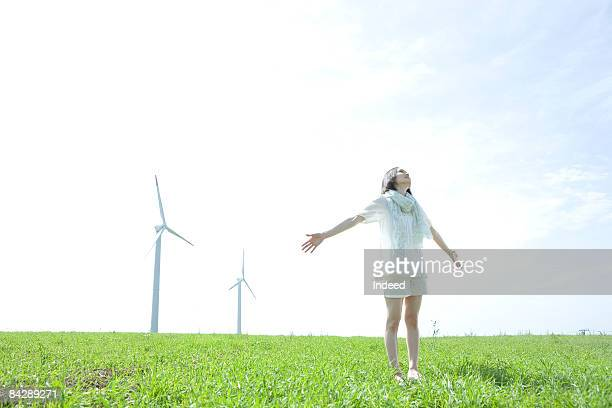 Japanese woman stretching arms on grass