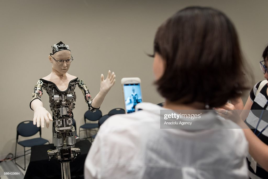 Japanese woman takes a photo of the humanoid robot called Alter designed by scientists in Japan as it is exhibited at the National Museum of Emerging...