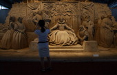 Japanese woman takes photograph of sand replica titled 'Absolute Monarchism Under the Regime of Queen Elizabeth I' during the event of sand made...