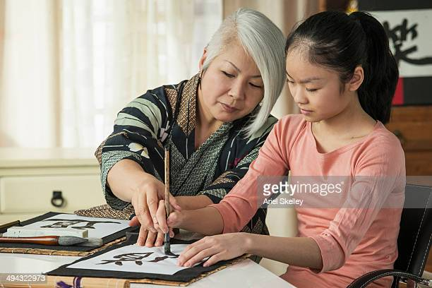 Japanese woman teaching granddaughter traditional calligraphy