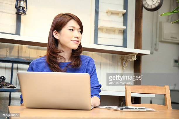 Japanese woman using laptop in cafe