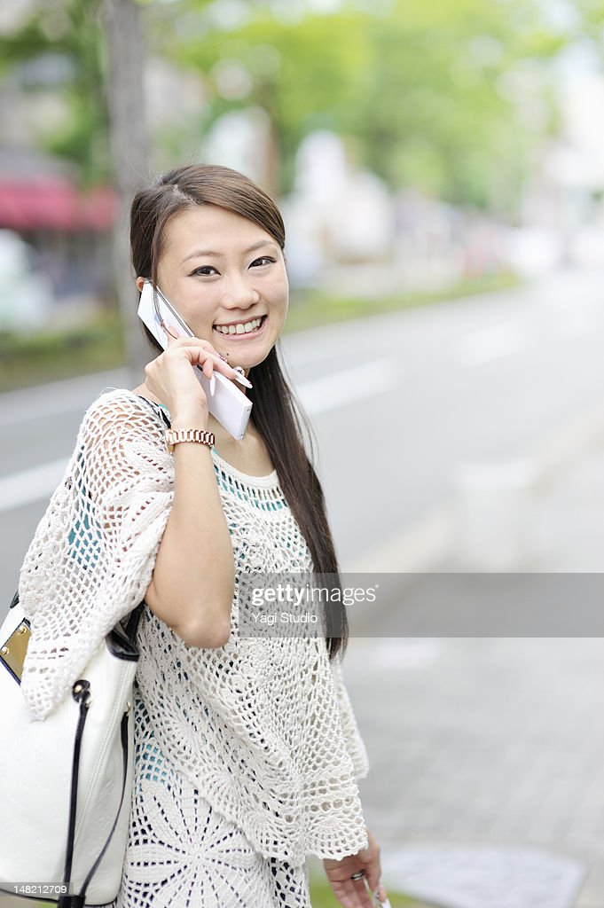 Japanese woman using mobile phone, smiling : Stock Photo