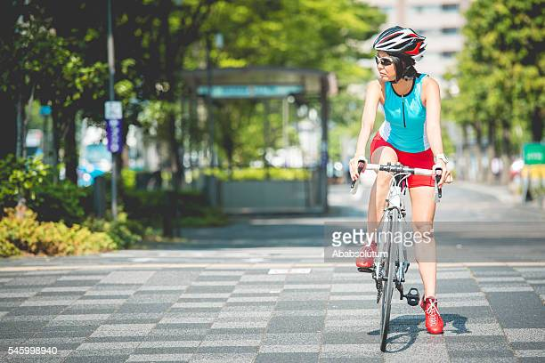 Japanese Woman Waiting while Riding Bike in Kyoto City, Japan