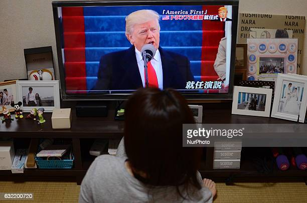 A Japanese woman watches TV news reporting 45th US President Donald Trump's inauguration ceremony at a discount chain store in Tokyo Japan January 21...