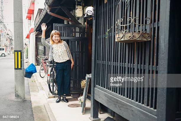 Japanese Woman Waves From Entrance to Her Kyoto Japan Store