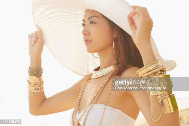 Japanese woman wearing gold bracelets and sun hat