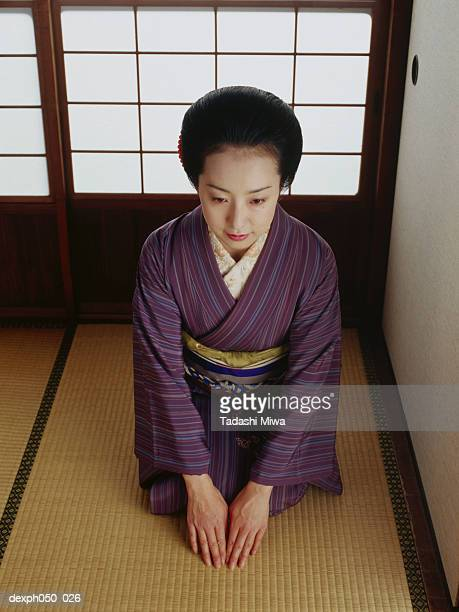 Japanese woman wearing kimono, sitting on floor