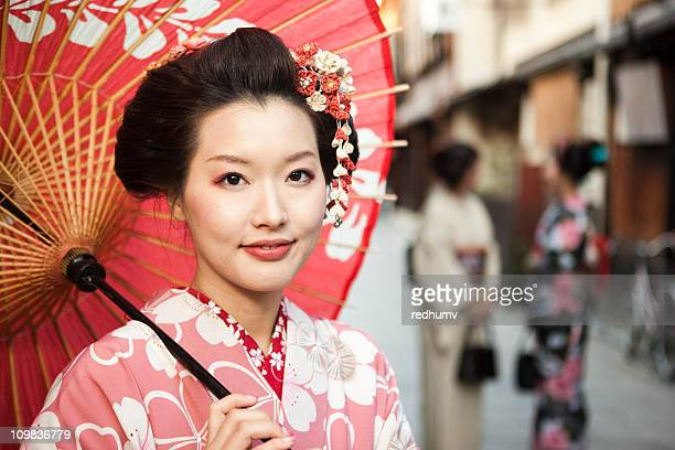 Japanese woman with a red umbrella in Kyoto, Japan