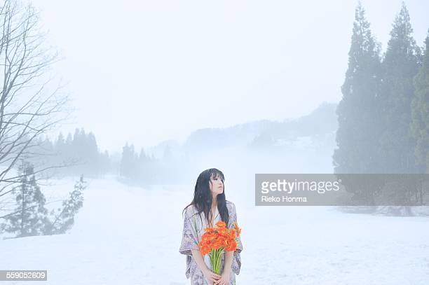 Japanese woman with flowers in snow