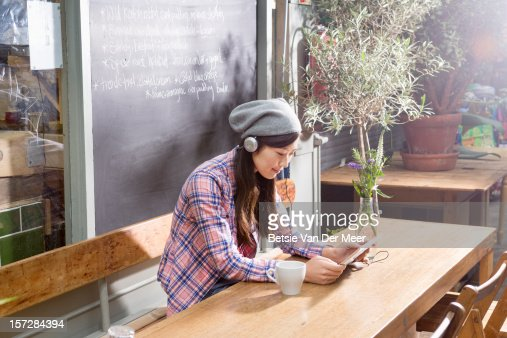 Japanese woman with ipad sitting in urban cafe. : Foto de stock