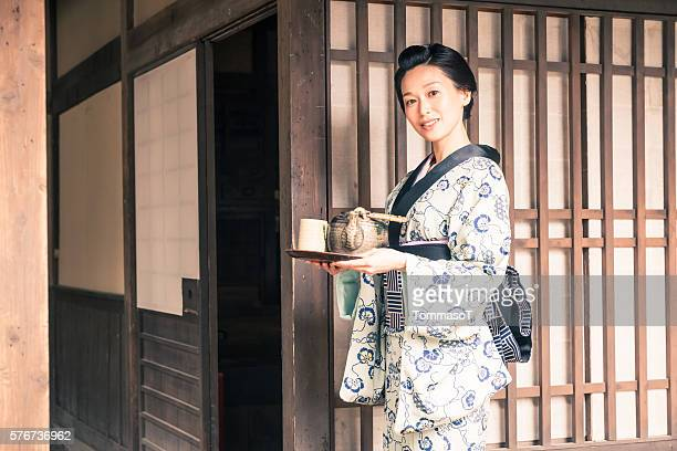 Japanese woman with tea tray and traditional kimono dress