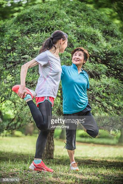 Japanese women in park stretching legs before a run