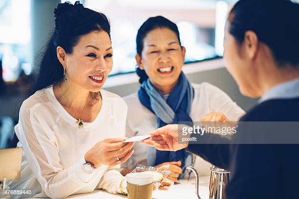 Japanese women making payment with credit card in cafe