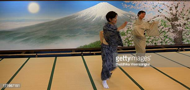 Japanese women perform a traditional dance in front of the Mount Fuji painting at Sengentaisha Shrine on June 30 2013 in Fujinomiya Japan Every year...