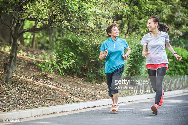 Japanese women running side by side in park