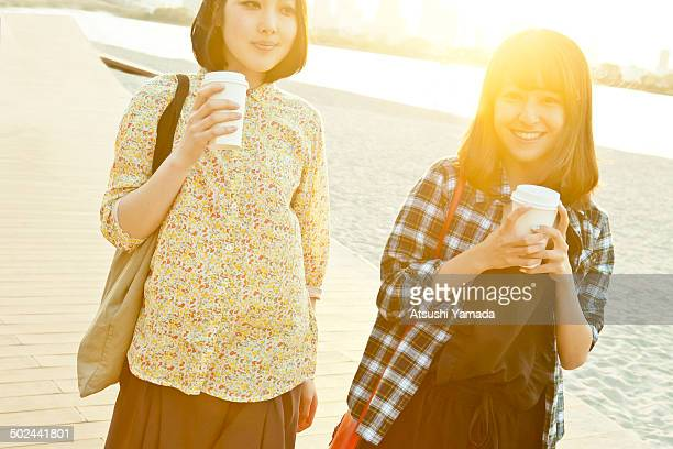 Japanese women walking along beach with coffee