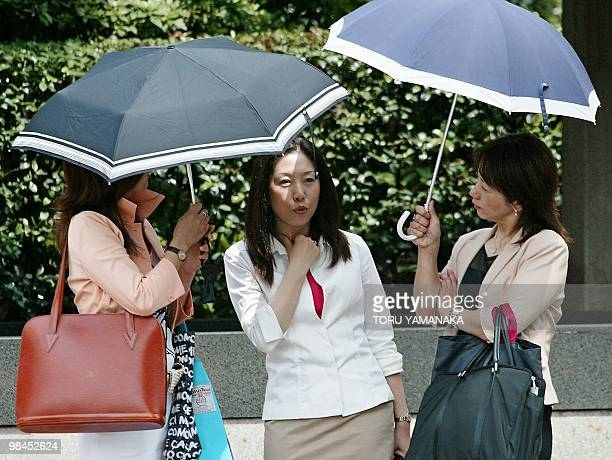 Japanese women with umbrellas to avoid ultraviolet chat on the street in downtown Tokyo 19 June 2003 With their sunhats ultraviolet filtering...