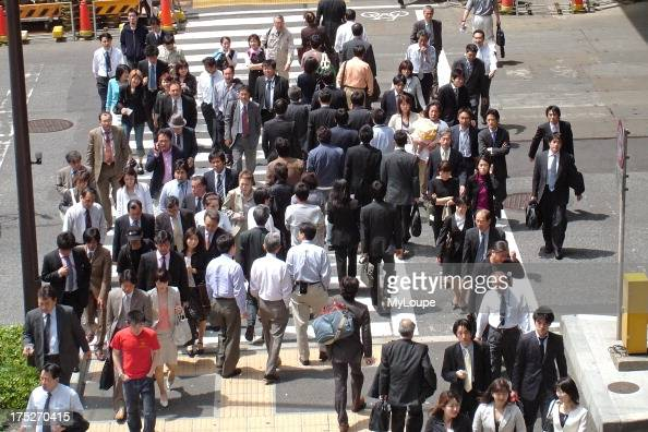 Japanese workers walking to work in downtown Tokyo Japan Asia