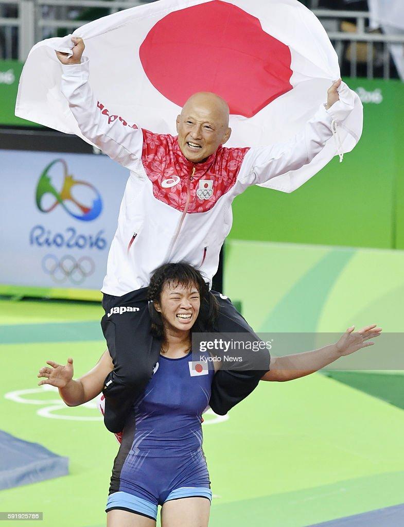 Japanese wrestler Risako Kawai carries team director Kazuhito Sakae on her shoulders after winning the gold medal in the women's freestyle 63kilogram...