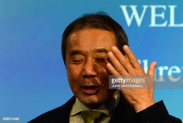 Japanese writer Haruki Murakami shields his eyes to avoid photographers' flash as he poses with his trophy prior to an award ceremony for the...
