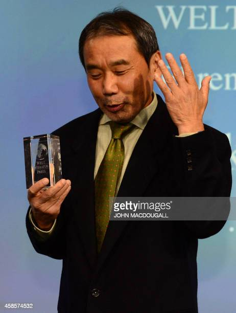 Japanese writer Haruki Murakami shields reacts as he poses with his trophy prior to an award ceremony for the Germany's Welt Literature Prize...