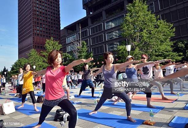 Japanese yoga students participate in an outdoor yoga class before going to work in front of Tokyo station in the Marunouchi financial district in...