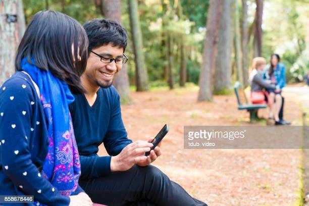 Japanese young couple sitting a bench outside using a phone