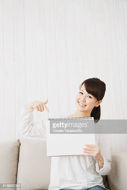 Japanese young woman in a white shirt with sketchbook on the sofa