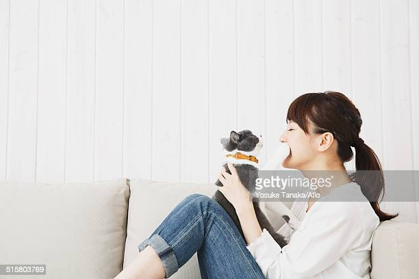 Japanese young woman in jeans and white shirt with cat on the sofa