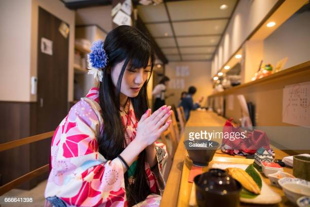 Japanese young woman in Kimono praying before lunch