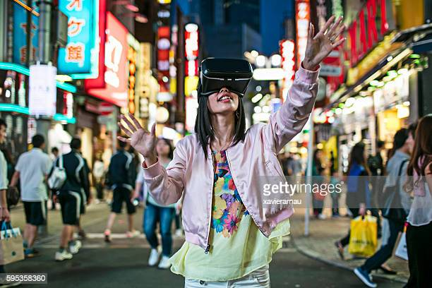 Japanese young woman using VR headset in the street