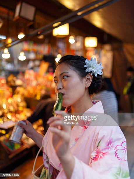 Japanese Yukata woman eating cucumber pickles with beer at festival
