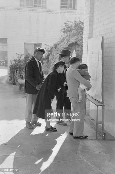 JapaneseAmericans Reading Evacuation Orders on Bulletin Board at Mary Knoll Mission During Evacuation of JapaneseAmericans from West Coast Areas...