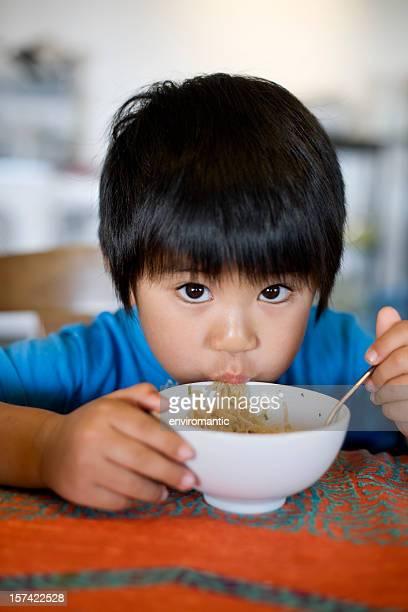 Japanese/Asian boy eating instant noodles.