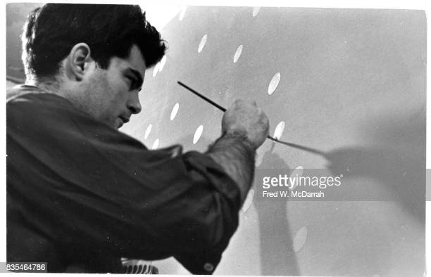 Japaneseborn American artist Lawrence 'Larry' Poons works on a painting in his Greenwich Village loft New York New York February 2 1965