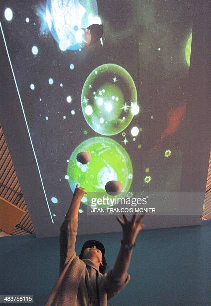 Japanese's artist Yuri Kimura throws balls to a projected image on a ceiling as she plays with a virtual reality game created by the Japanese...