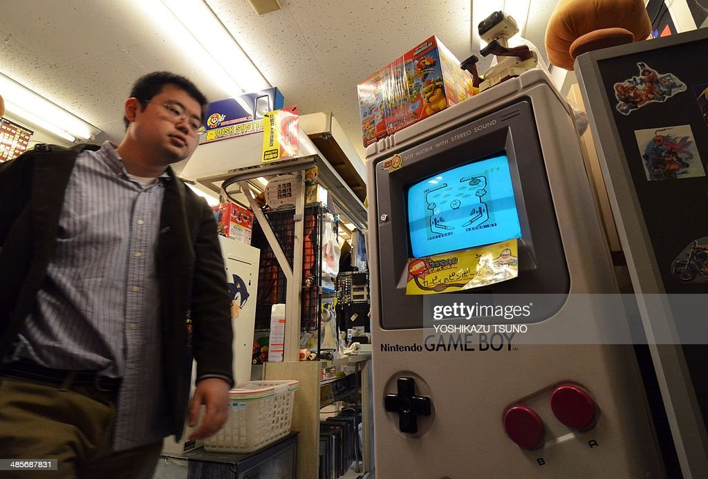 Japan-Lifestyle-entertainment-game-company-Nintendo-GameBoy by Miwa SUZUKI This picture taken on April 17, 2014 shows a customer looking at a large mock-up of videogame console Game Boy at a videogame shop in Tokyo, while a large figure of Nintendo's character Super Mario stands. Nintendo's trailblazing Game Boy marks its 25th anniversary Monday with the portable device's legacy living on in cutting-edge smartphone games and among legions of nostalgic fans. AFP PHOTO / Yoshikazu TSUNO