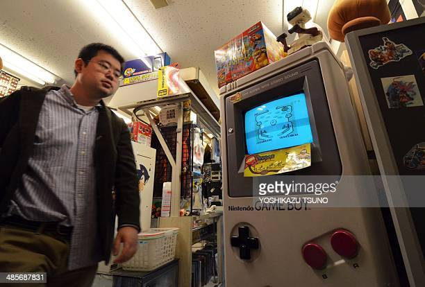 JapanLifestyleentertainmentgamecompanyNintendoGameBoy by Miwa SUZUKI This picture taken on April 17 2014 shows a customer looking at a large mockup...
