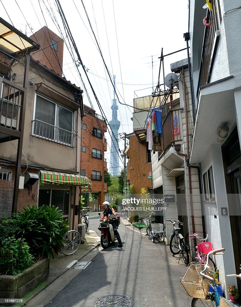 STORY 'JAPAN-quake-fire' BY A postman drives a motorcycle through a narrow alley to deliver mail at Tokyo's Sumida ward, with the Tokyo Sky Tree in the background on September 6, 2012, University of Tokyo Earthquake Research Institute associate professor Shinichi Sakai has warned a possible risk of an earthquake under Tokyo. The Great Kanto Earthquake, which occured in 1923 in the Tokyo area killed more than 140,000 people. AFP PHOTO / Jacques LHUILLERY