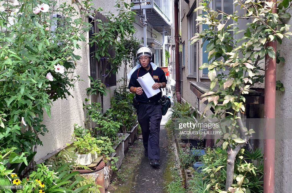 STORY 'JAPAN-quake-fire' BY JACQUES LHUILLERY A postman makes his way through a narrow alley to deliver mail at Tokyo's Sumida ward on September 6, 2012. University of Tokyo Earthquake Research Institute associate professor Shinichi Sakai has warned a possible risk of an earthquake under Tokyo. The Great Kanto Earthquake, which occured in 1923 in the Tokyo area killed more than 140,000 people. AFP PHOTO / Jacques LHUILLERY