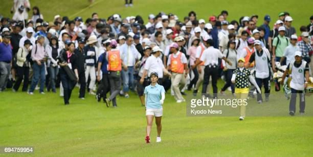 Japan's Ai Miyazato is followed by a large crowd during the final round of the Suntory Ladies Open golf tournament at Rokko Kokusai Golf Club in Kobe...
