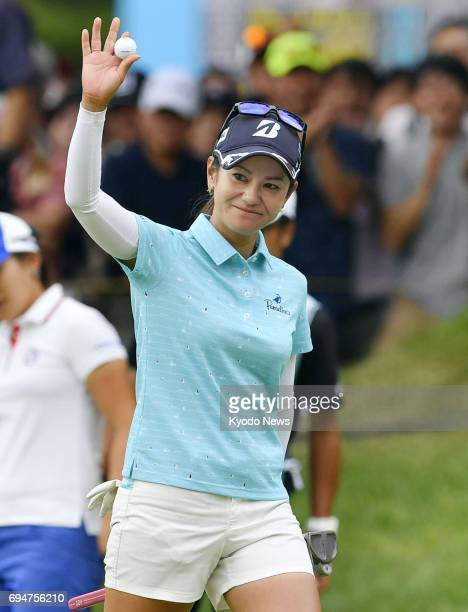 Japan's Ai Miyazato waves to the gallery after making a par putt on the 18th green in the final round of the Suntory Ladies Open golf tournament at...