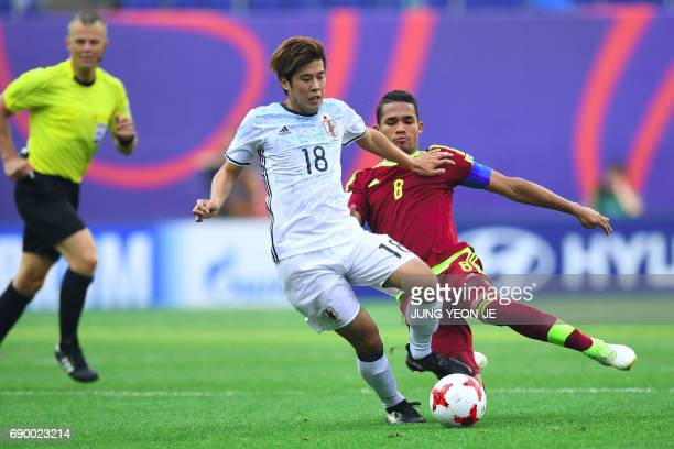 Japan's Akito Takagi fights for the ball with Venezuela's Yangel Herrera during their U20 World Cup round of 16 football match between Venezuela and...