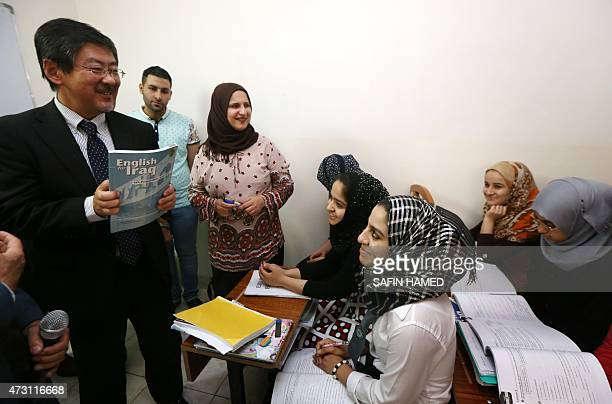 Japan's ambassador to Iraq Kazuya Nashida speaks to Syrian and Iraqi refugees during a launching ceremony of a UN sponsored educational project at...