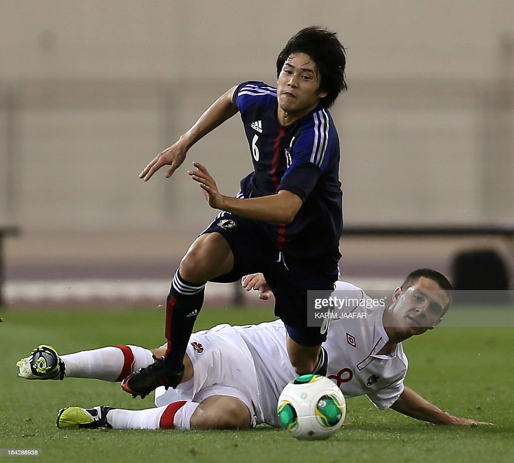 Japan's Atsuto Uchida advances with the ball past Canada's William Johnson during their friendly football match at Khalifa Stadium in the Qatari...