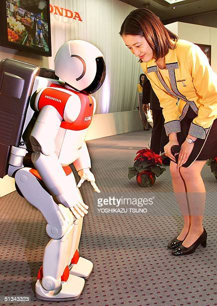 Japan's auto giant Honda employee Michiko Suzuki exchanges bows with Honda's humanoid robot Asimo 12m in height and weighing 43kg during the yearend...